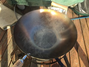 A carbon steel wok on a propane burner